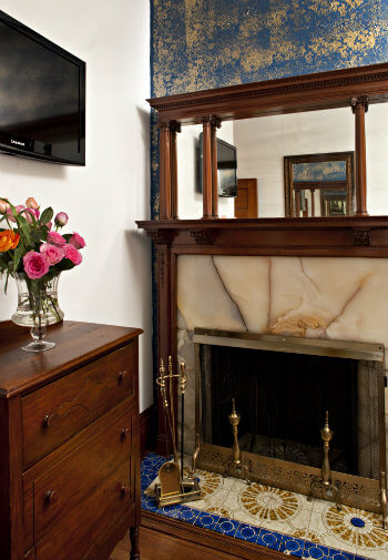 Fireplace with tan marble surround and brass fittings