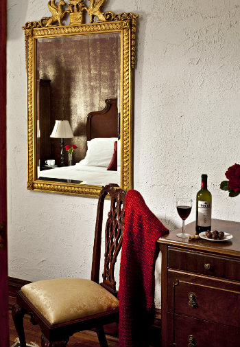 Gold framed mirror, chair with red throw and wood side table
