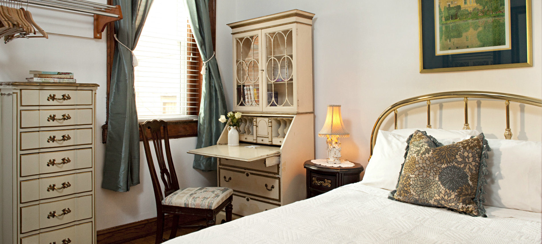 White covered bed with white and gilt writing desk and chair