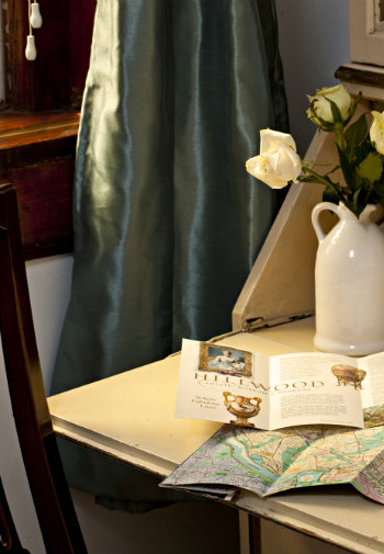 maps on desk with jug of white roses