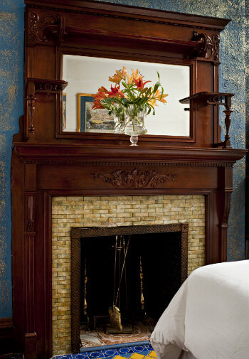 Fireplace with white tile surround and wooden mantle with mirror
