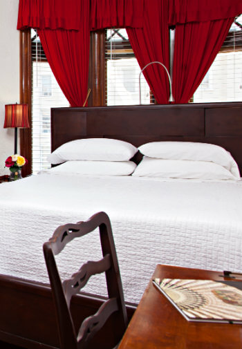 Large wooden bed with white bedding and adesk with a chair